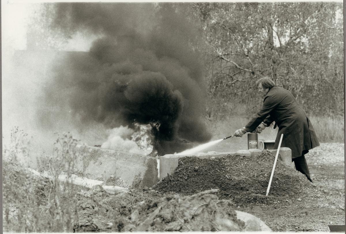 Lars Johansson på utbildning i brandförsvar hos Trafikaktiebolaget Grängesberg - Oxelösunds Järnvägar, TGOJ i Eskilstuna 1986. Här kväver han elden på brinnande olja med pulversläckare.