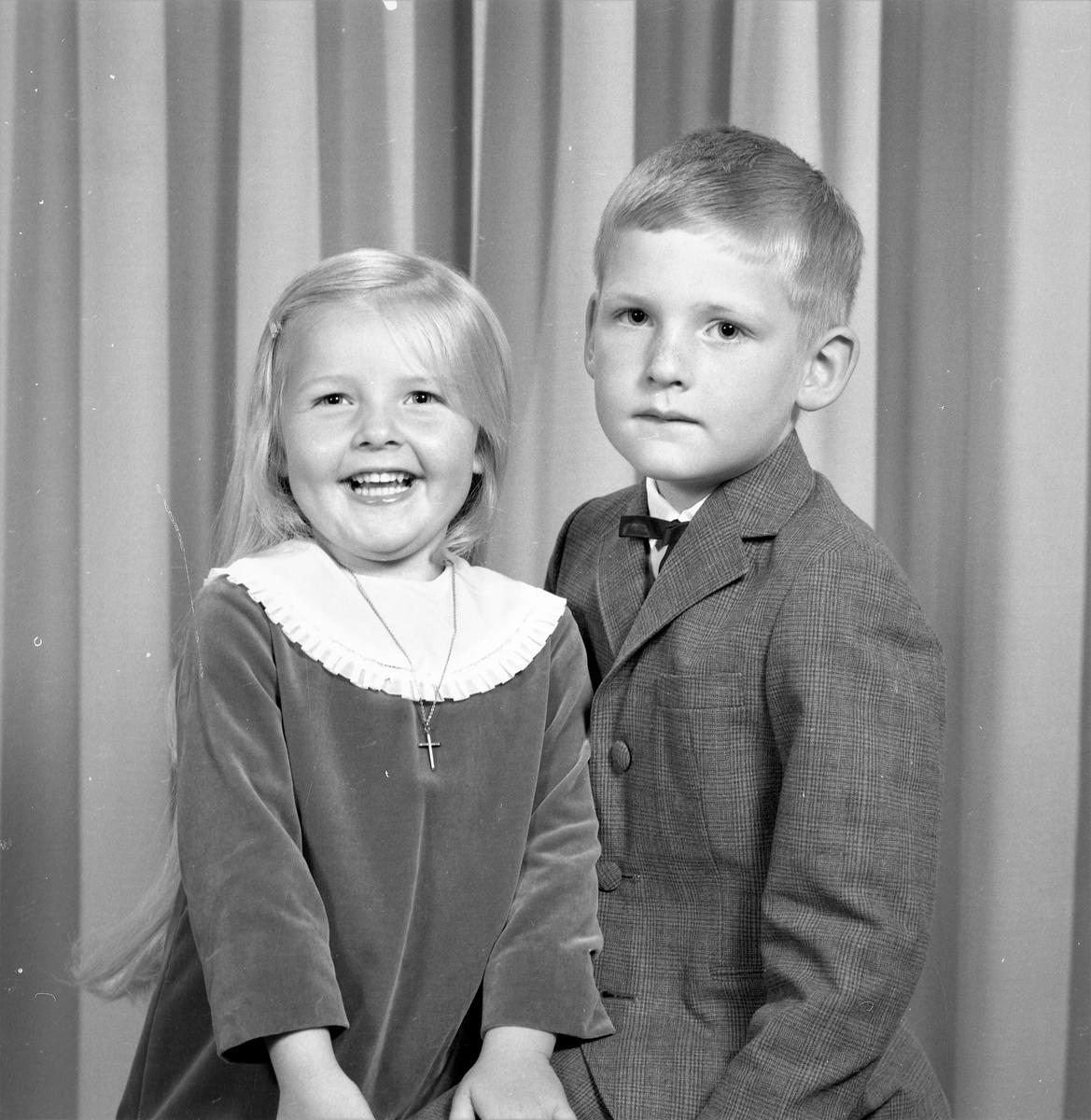Portrett. Familiegruppe på to barn. Søsken. Ung lyshåret pike i mørk velurkjole med stor lys krage. Kors i kjede om halsen. Ung  lyshåret gutt med mørk rutet dress, hvit skjorte og mørk sløyfe. Bestilt av Egil Andersen. Moksheim