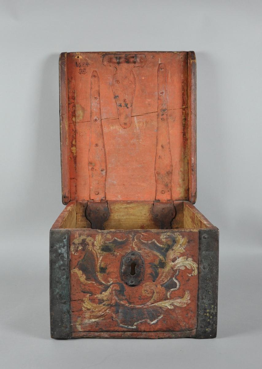 Ferdaskrin med rosemaling og metallbeslag på alle hjørner og på lokket. Ryggen på skrinet skrår utover øverst, slik at det er mindre plass i bunnen.