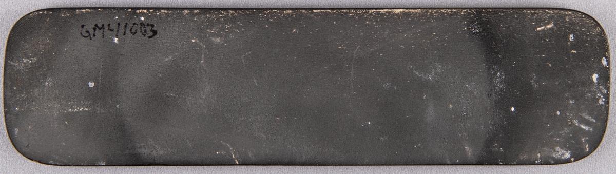Skylt i svart med stämplad dekor, texten lyder: lillemor Mannerheim.