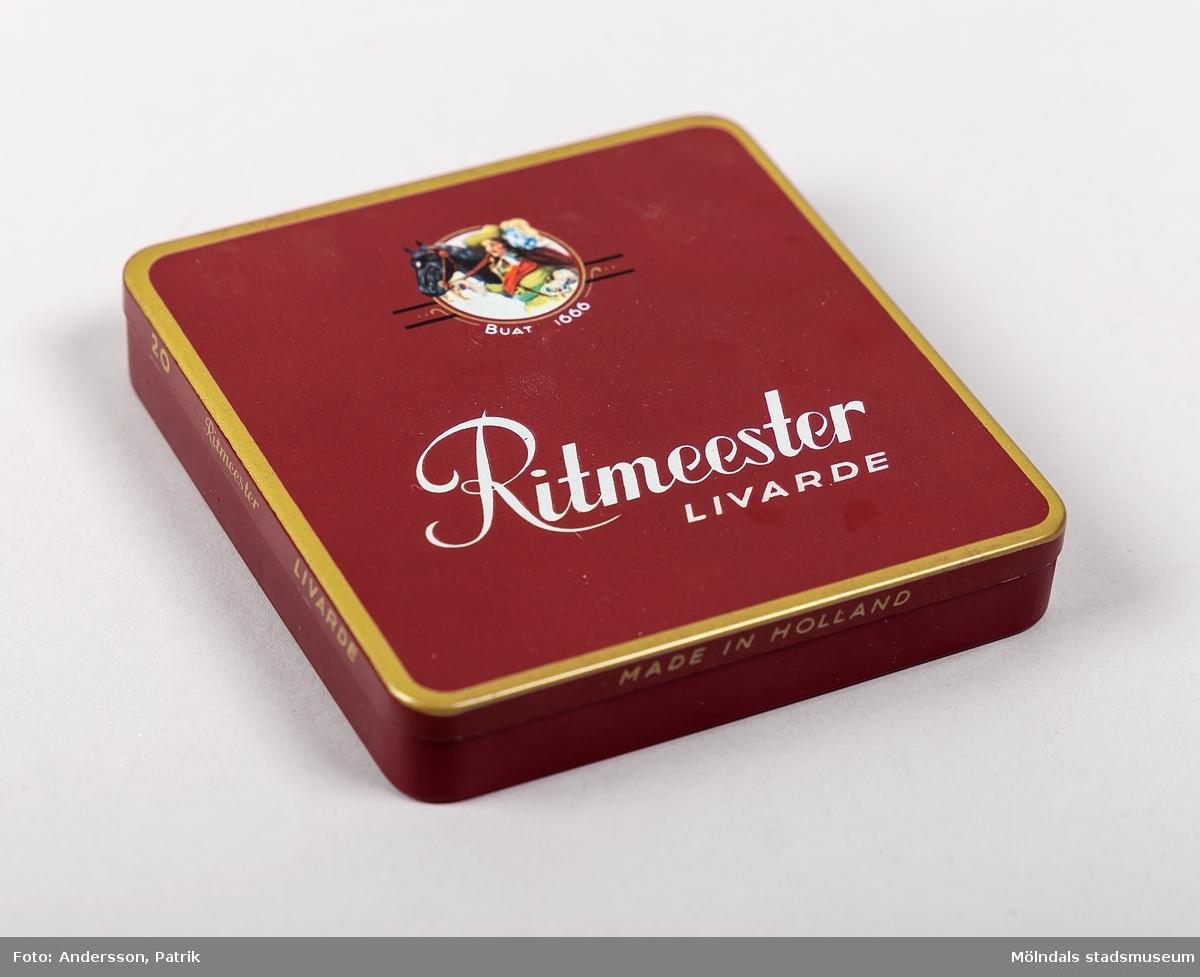 """Plåtask som har innehållit 20st cigariller tillverkade av Ritmeester, troligtvis på 1960-talet.  Asken är röd och är guldfärgad längs kanterna. På sidorna finns texten:  """"20  Ritmeester  LIVARDE     MADE IN HOLLAND"""",  På askens ovansida och insida finns Ritmeesters logga tillsammans med texten: """"Ritmeester LIVARDE""""."""