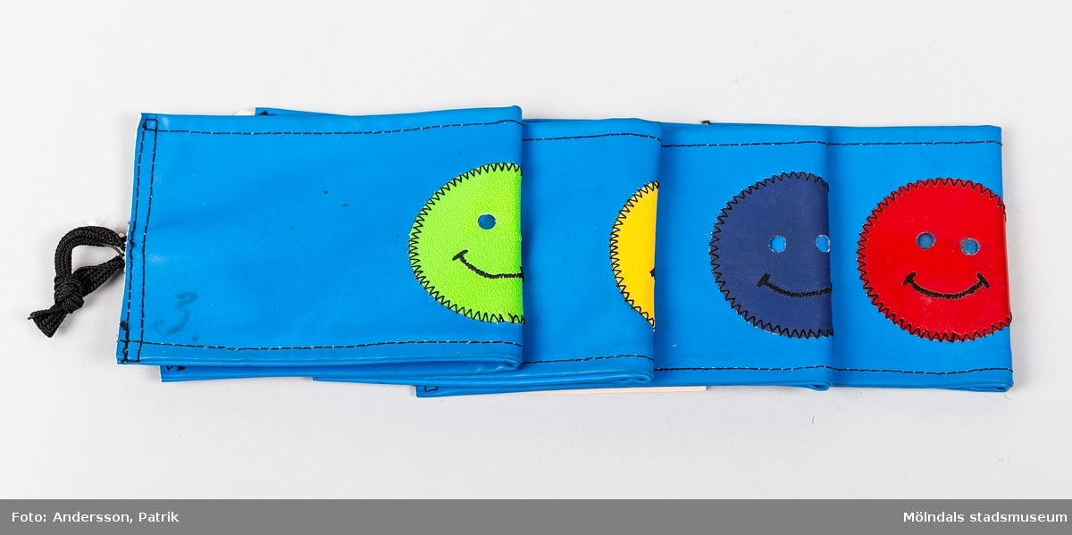 """4 st blå armbindlar utgivna av Trafiksäkerhetsverket på 1970-talet. Varje armbindel har varsin smiley och handskriven siffra. 1 st med gul smiley och siffran """"2"""". 1 st med grön smiley och siffran """"3"""". 1 st med röd smiley och siffran """"4"""". 1 st med blå smiley och siffran """"4""""."""