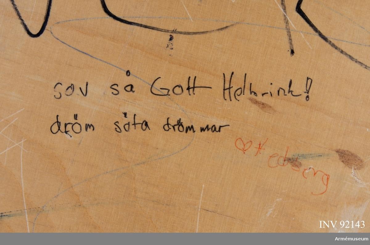 Sängbotten i trä avsedd för våningssäng i metall. Nedklottrad med text och bilder av mestadels sexistisk karaktär. Flertalet kommentarer berör muck och värnpliktens vardag i övrigt. En klisterlapp med Sjöfartsverkets tio sjövettsregler, liksom fem mindre klisterlappar från snusdosor av märkena Göteborgs rapé och General är fastsatta.