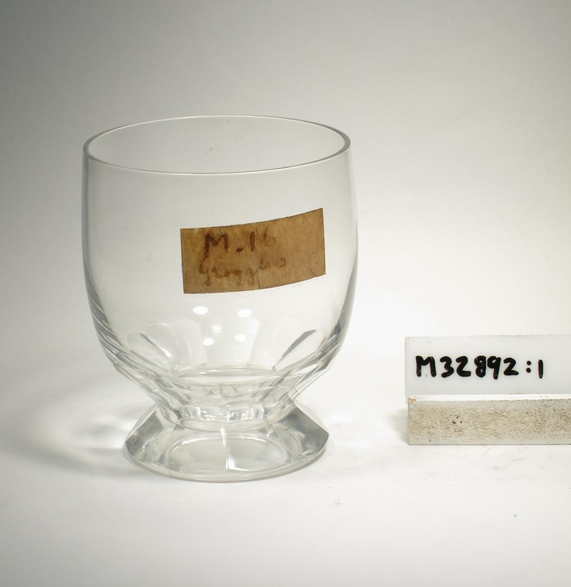 "Svagt elliptisk kupa på konisk klack. Glaset är facettslipad i 9 bågar. Lapp: ""M.16 Grogglas"""