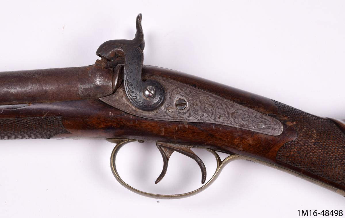 Hagelgevär, dubbelpipigt, kolven skuren med detaljerat hjorthuvud i relief och högrelief, samt lagerkrans i relief.