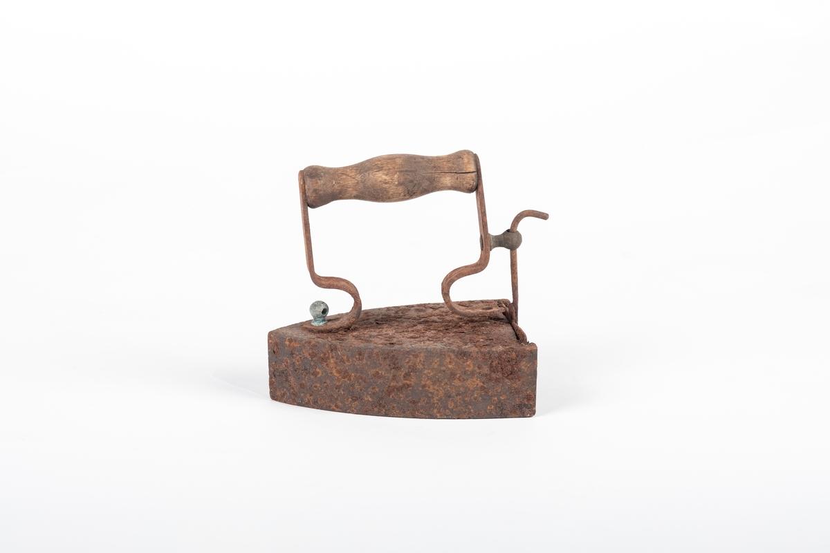 Spisst, ovalt med rett ende. Håndtak i tre festet med flate, buede metallstenger. Håndtaket er festet til jernet med skrue og knott. Hulrom inni med stengsel foran til det oppvarmete jernet. Stengselet har en stang som går gjennom et feste koblet til selve jernets håndtak.