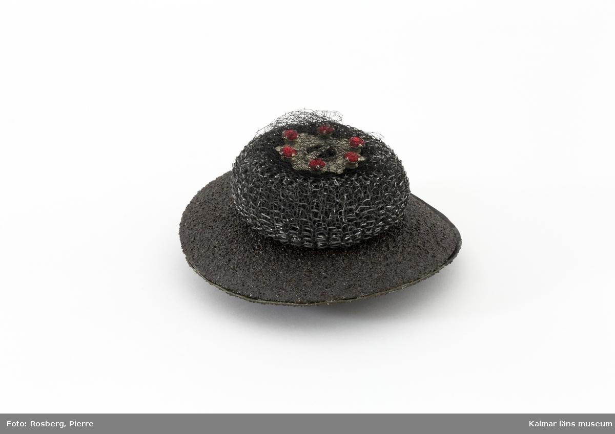 Tredimensionellt konstverk byggt i lager med runda former, olika material och färger i grått, svart och rött.