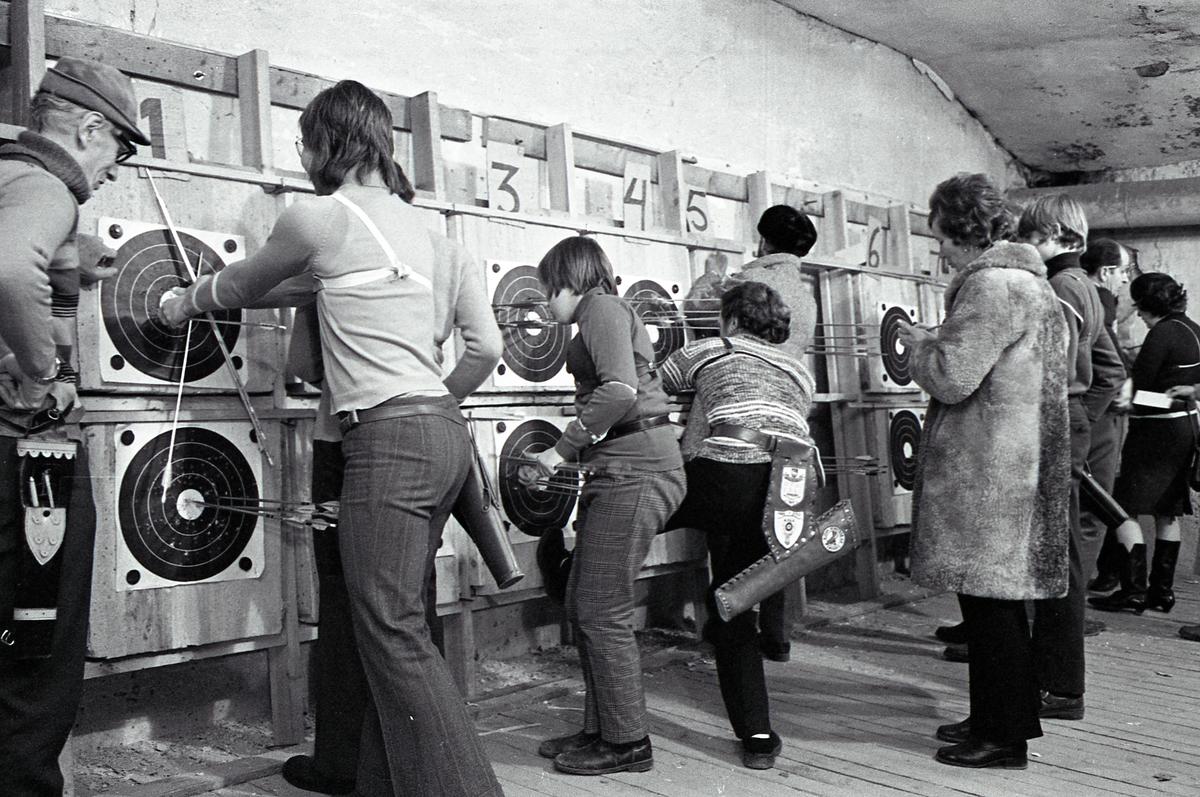 Inomhusträning i bågskyttelokalen. Skyttar, i varierande ålder, plockar bort sina pilar från måltavlorna. Måltavlorna är placerade i dubbla rader längs kortväggen i källarlokalen. Kvinnan i päls är Kerttu Klotz.
