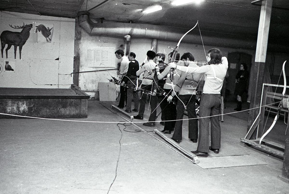 Inomhusträning hos Arbogas Bågskytteklubb. Skyttarna står uppställda, på rad, med pil och båge. På väggen syns viltdjursaffischer. Lokalen ser ut att ligga i en källare.