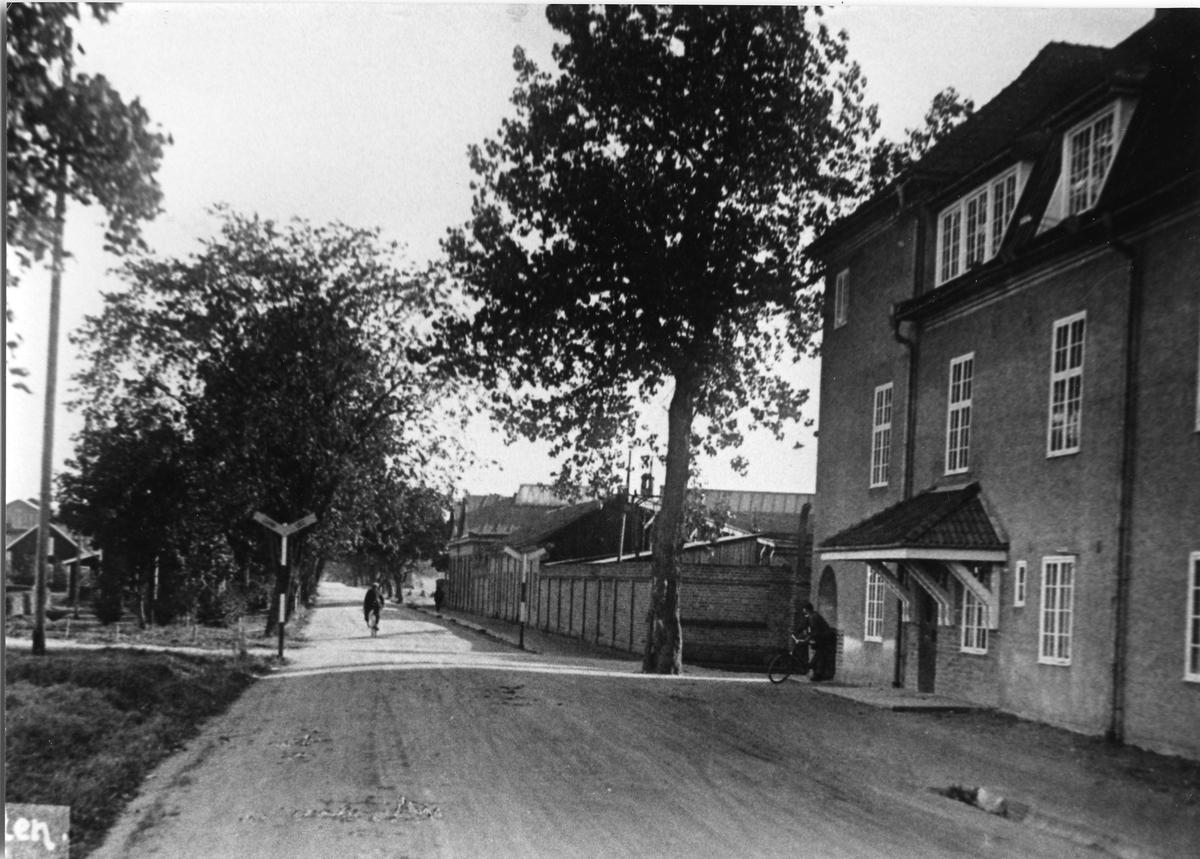 Entrén till Arboga Mekaniska Verkstad på Jädersvägen Två män på cykel  Arboga Mekaniska Verkstad var först i landet med att installera en elektrisk motor för drift av verktygsmaskiner vid en taktransmission (1887).