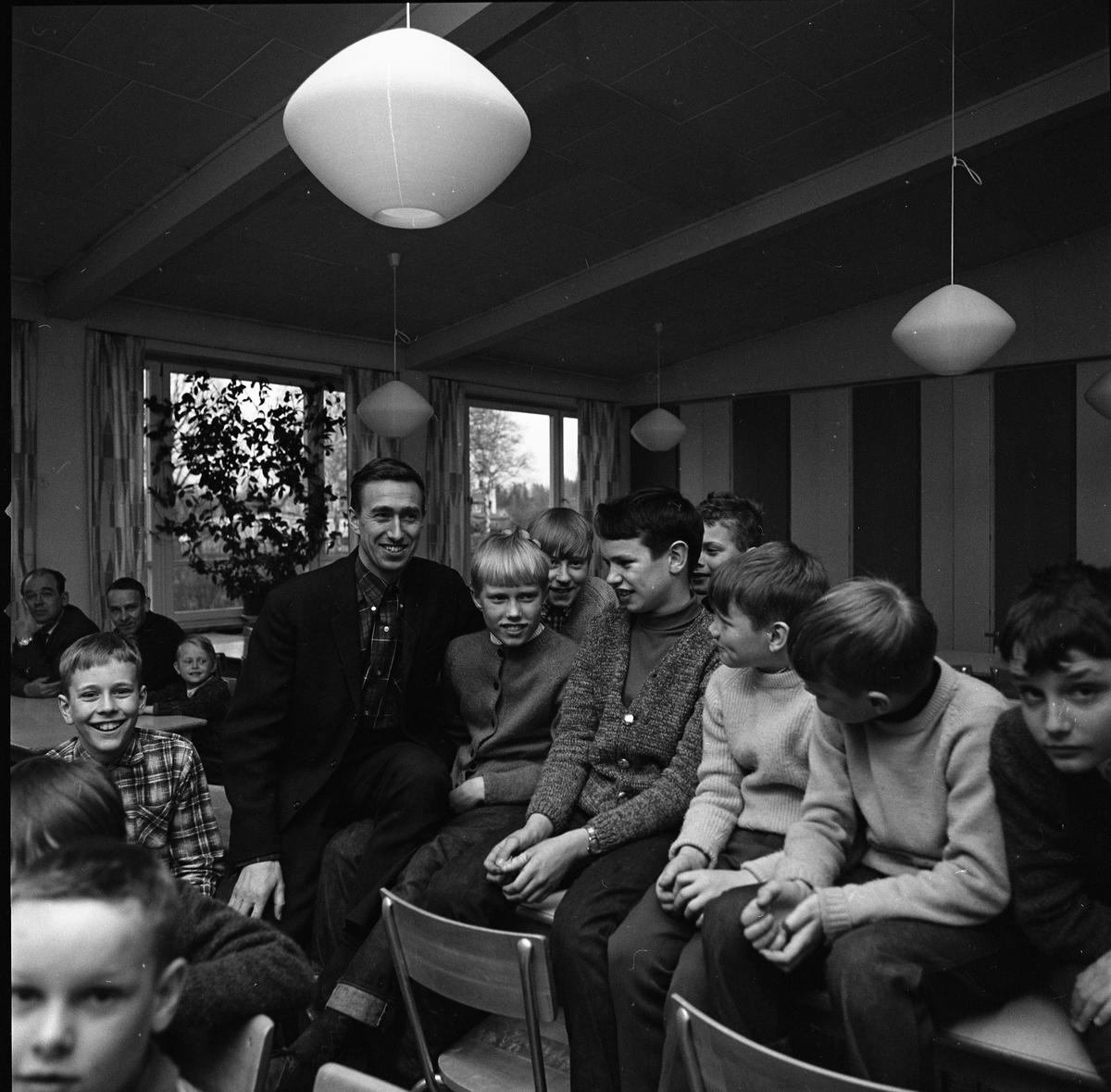 Arboga Orienteringsklubb har ungdomsträff. Man omgiven av pojkar. Två andra män skymtar i bakgrunden. Mannen är Lennart Öberg, orienterare. Bilden är tagen i Gäddgårdsskolans matsal.