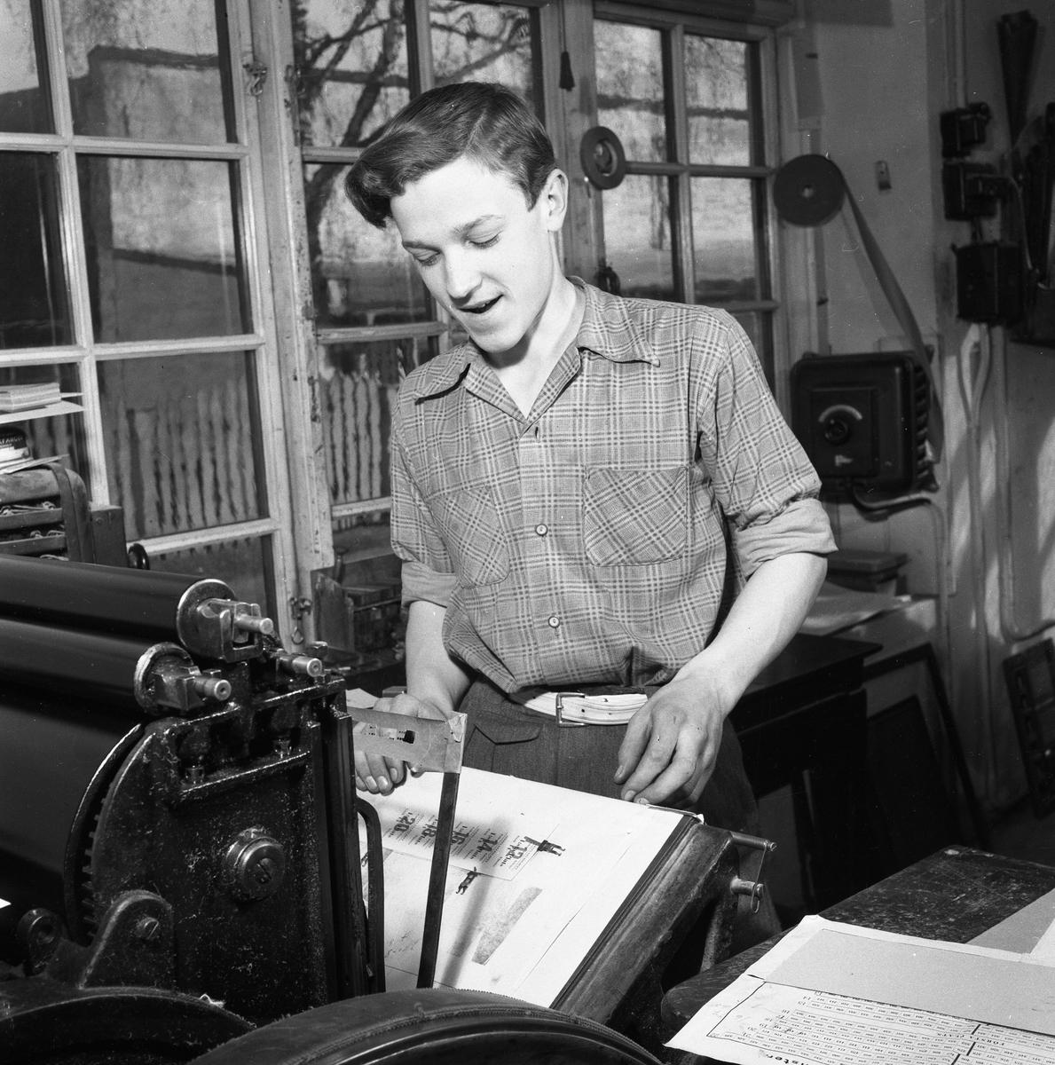 Arboga Tidning, interiör. En ung man, med uppkavlade skjortärmar, arbetar vid en maskin i tryckeriet.