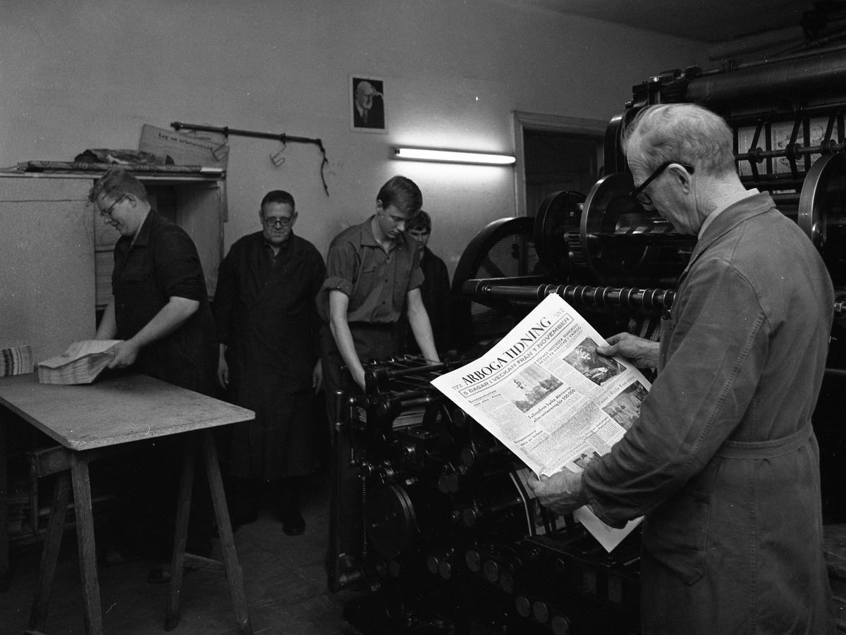 Arboga Tidning, personal och interiör. Fem män står i tryckeriet. Nummer två från vänster är Nils Munther. En man håller i en bunt tidningar, en annan man håller i ett färskt exemplar.