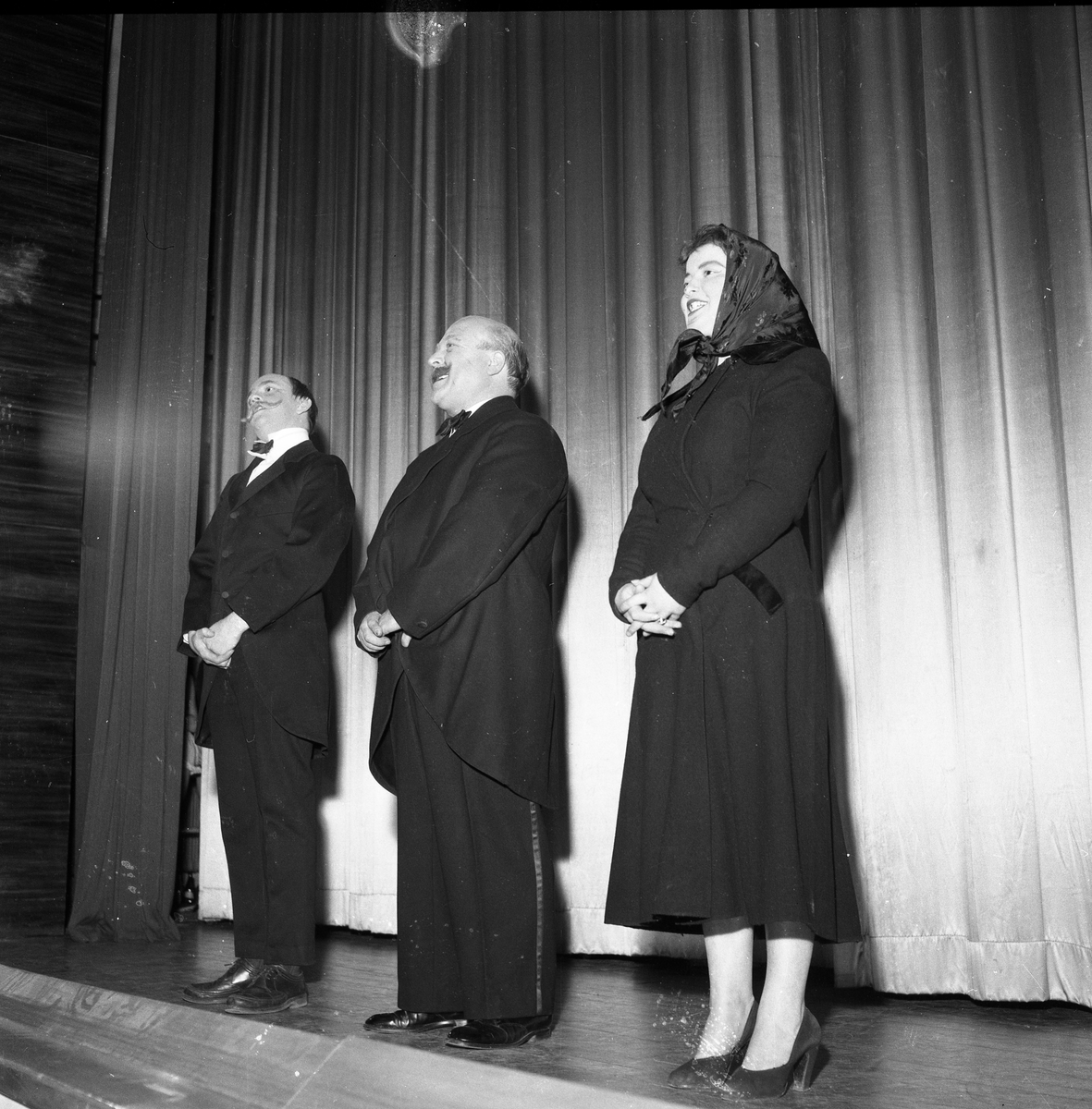 Arbogarevyns medlemmar spelar upp sin Jubileumsrevy. Tre personer står på scenen, två klädda i frack och den tredje i kappa och sjalett.