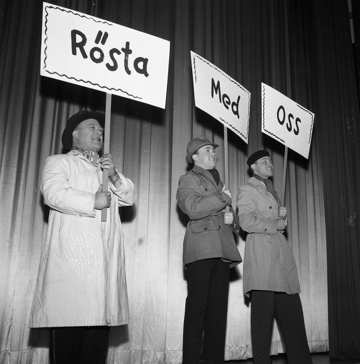 Arbogarevyns medlemmar sätter upp sin Jubileumsrevy. Tre män på scenen. De bär plakat och ytterkläder.