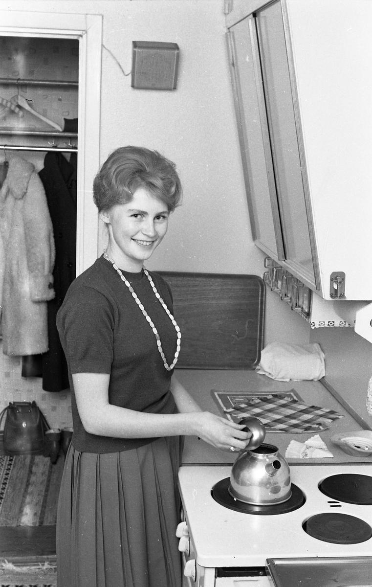 Kerstin Eklund, Arbogas Lucia, står i köket och kokar kaffe. Spisen har tre plattor. Under överskåpet hänger specerilådor. I hallen hänger en fårskinnskappa. En väska och ett par stövletter står på golvet.