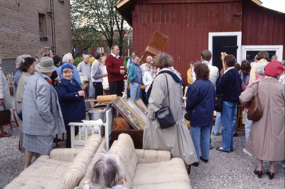 Auktion, utomhus. Auktionsförrättaren står mitt i bild med klubban i handen. Någon håller upp en stol för utrop. En soffgrupp står på grusplanen. Människor, i ytterkläder.