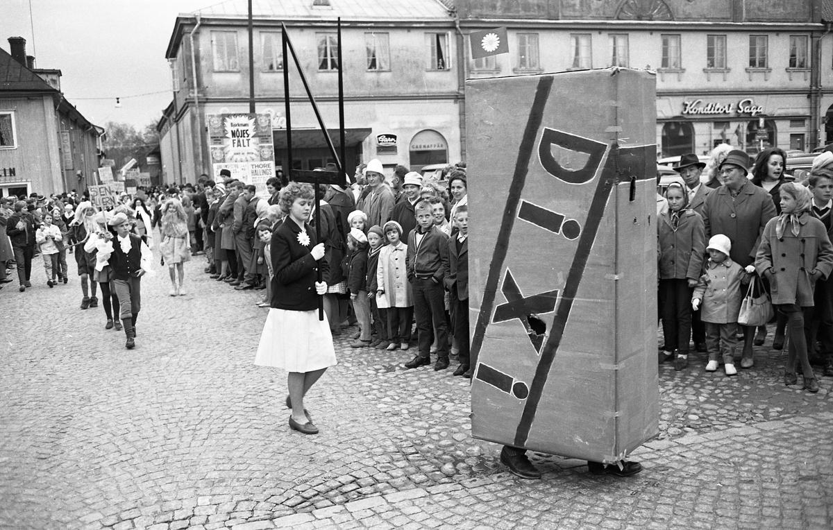 Barnens Dag firas med en barnparad. Här kommer en Dixi-kola följd av en flicka med en Barnens-Dags-blomma på kavajslaget. Bakom henne kommer en grupp stenåldersmänniskor med långa skägg. En stor publik har samlats på Stora torget för att titta på.