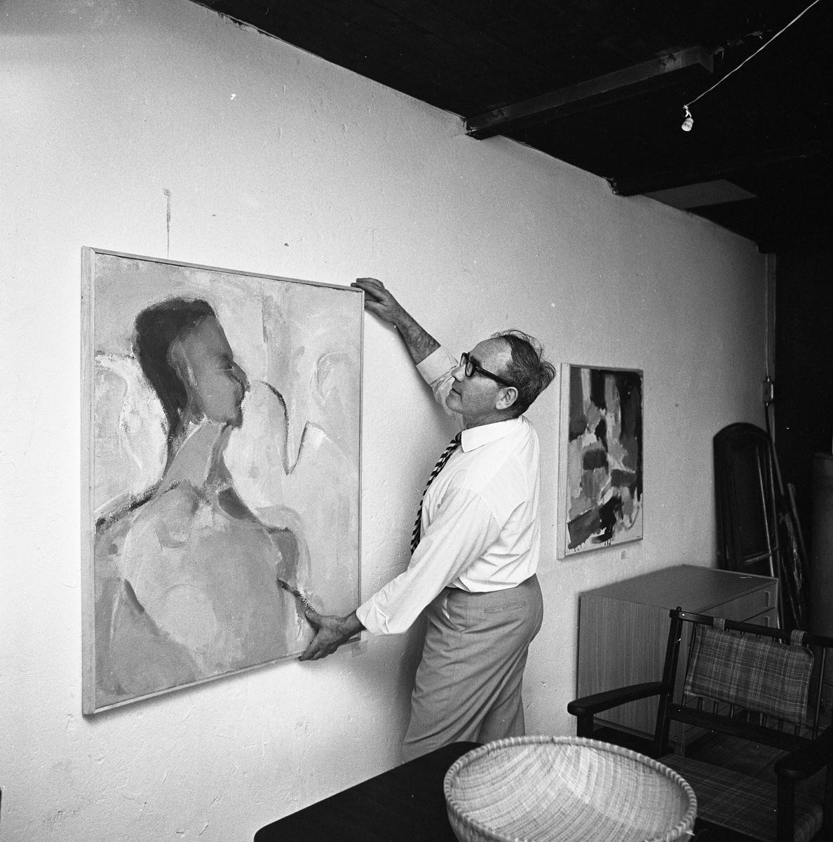 Bertil Levin ordnar konstutställning i Stallet, Västerlånggatan 1. Man som hänger upp en tavla. Några möbler skymtar.