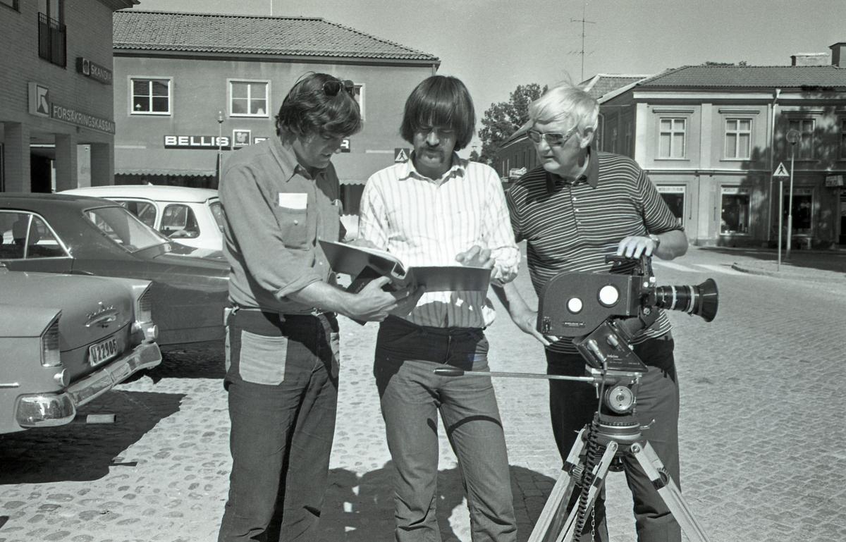 Bo Teddy Ladberg (till höger) gör en film om schack. Han har en filmkamera på stativ. Två andra män tittar i manus. Försäkringskassan till vänster, Bellis blommor i bakgrunden. Bilar är parkerade till vänster. Männen står på Järntorget.