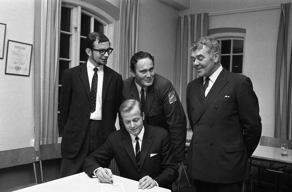 Utbildning för bryggeripersonal. De tre män som står upp, är utkörare. Från vänster: okänd, Kurt Jansson och Mats Tängvall. Mannen som sitter är okänd. På väggen hänger ett diplom från Korpen. Arboga Bryggeri