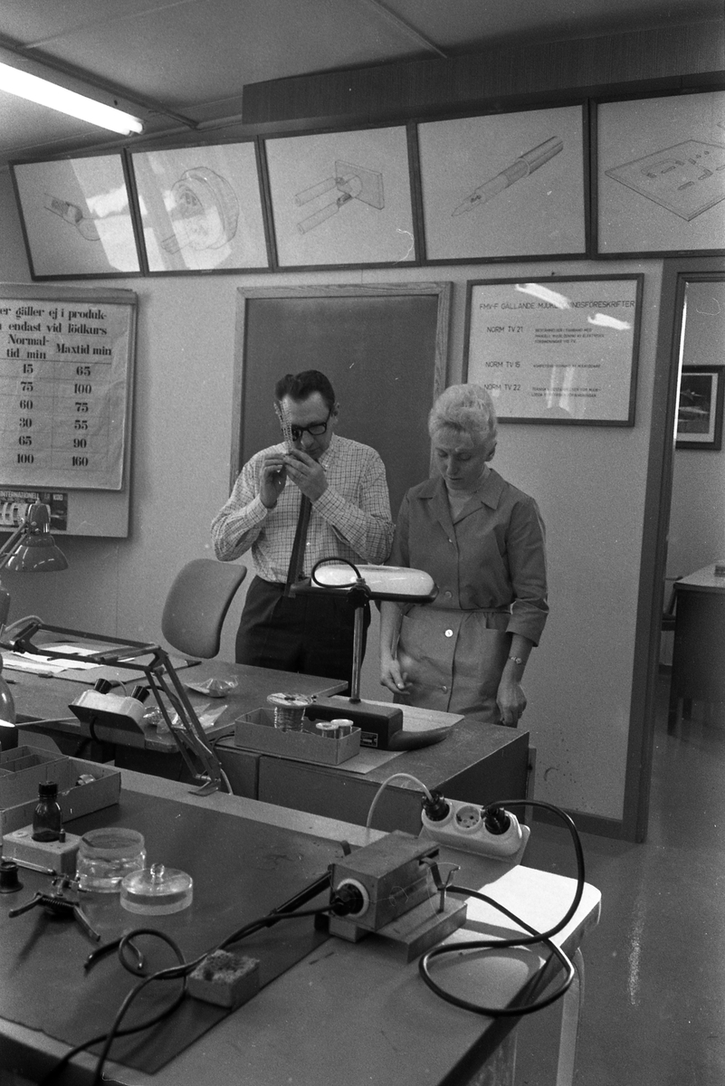 Bertil Jakobsson håller kurs i lödning på CVA. En kvinnlig elev står intill honom. Arbetsbord med verktyg och lampor. Centrala Verkstaden Arboga