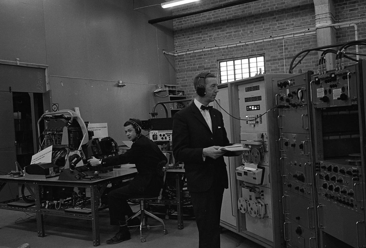 CVA interiör. Autotestare. Två män, iförda hörlurar, arbetar med stora instrument. Mannen som står upp heter Lennart Thornström. Centrala Verkstaden Arboga
