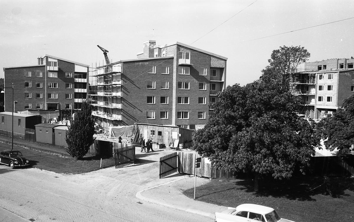 Vilstaområdet får flerfamiljshus. Byggnation längs Lundborgsesplanaden. Arbetskupor är uppställda. En lyftkran syns över hustaken. Dokumentation av fastigheter i kvarteren söder och norr om ån. Bilder och beskrivning finns på Arboga Museum.