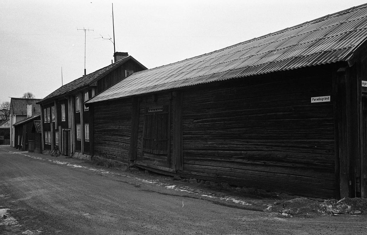 Exteriör av förråd/uthus i kvarteret Tullnären, hörnet Paradisgränd - Trädgårdsgatan. Uthuset har liggande timmer. Till vänster ses ett bostadshus i två våningar. Fotografens anteckning: Dokumentation av fastigheter i kvarteren söder och norr om ån. Bilder och beskrivning finns på Arboga Museum.