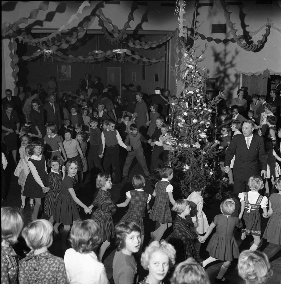 """FCTFs julfest på Folkets Hus Dans kring julgranen, föräldrar och barn, gamla och unga, deltar i  dansleken """"Små grodorna"""". Det är trångt på dansgolvet. Girlanger hänger i taket. Julgransplundring."""