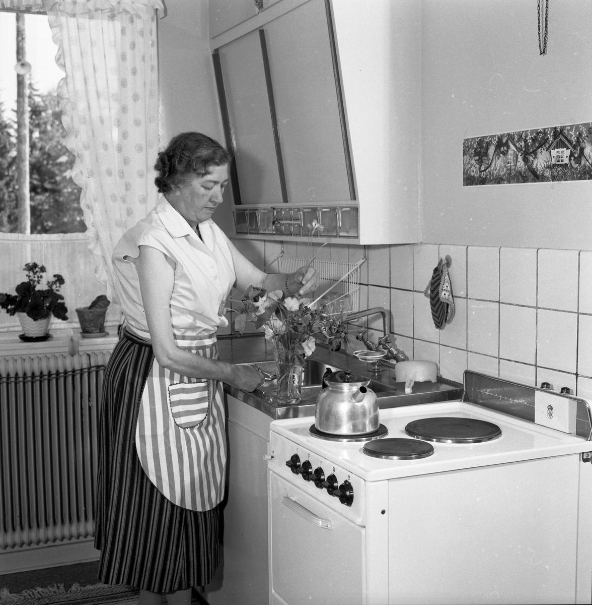 Fru Blomberg, (maka till Jakob Blomberg på Arboga Mekaniska Verkstad) i köket. Hon står vid diskbänken och arrangerar blommor i en vas. Kaffepannan står på spisen. Det står krukväxter på fönsterbrädan. AMV
