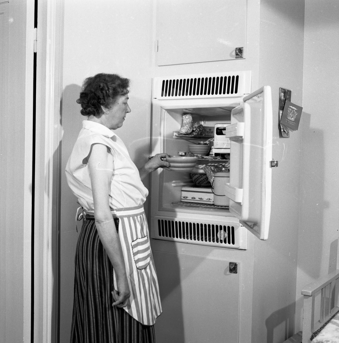 Fru Blomberg, hustru till Jakob Blomberg, på Arboga Mekaniska Verkstad, visar sitt kylskåp. I kylskåpet ses några skålar och en kakburk. En kökssoffa anas till höger. Kvinna, iklädd förkläde, står intill ett kylskåp. AMV