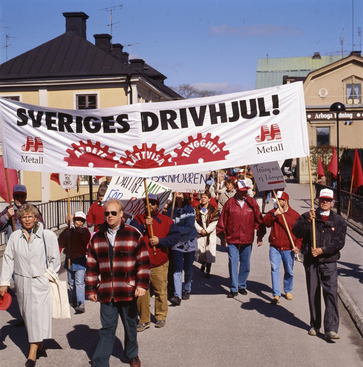 Första maj. Demonstrationståg på Kapellbron. Berit Oscarsson längst till vänster.  Människor marscherar med banderoller. I bakgrunden ses kvarteret Stadsgården till vänster och Kungsgården till höger. Socialdemokrater