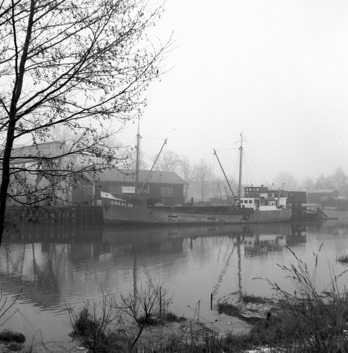 """Hamnen. En stor båt, vid namn Erkalin, ligger i hamnen. Vädret är disigt. Ett hamnmagasin syns bakom båten och längst till vänster, bakom trädet, skymtar """"lastningsröret"""" på Lantmännens silo. Bilden är tagen från Arbogaåns södra strand."""