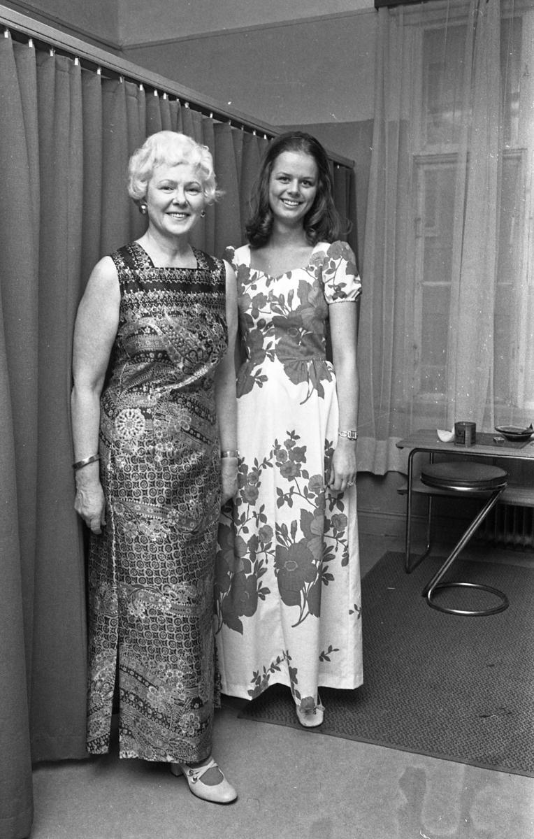 Det är dags för Öhrman & Melanders modevisning. Här står Harriet Larsson och Kerstin Löfgren i var sin långklänning. Harriet arbetar på Öhrman & Melander, där bilden är tagen.