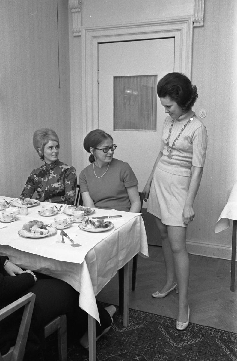 TBV ordnar modevisning och bjuder på kaffe och landgång. Vid bordet sitter Ann-Marie Törnqvist (blond) och Gulli Hammarlund (mörk) och studerar mannekängens jumper och kjol. Eftersom Sture Melander ses på en bild i sammanhanget, kan man gissa att kläderna kommer från Öhrman & Melander.