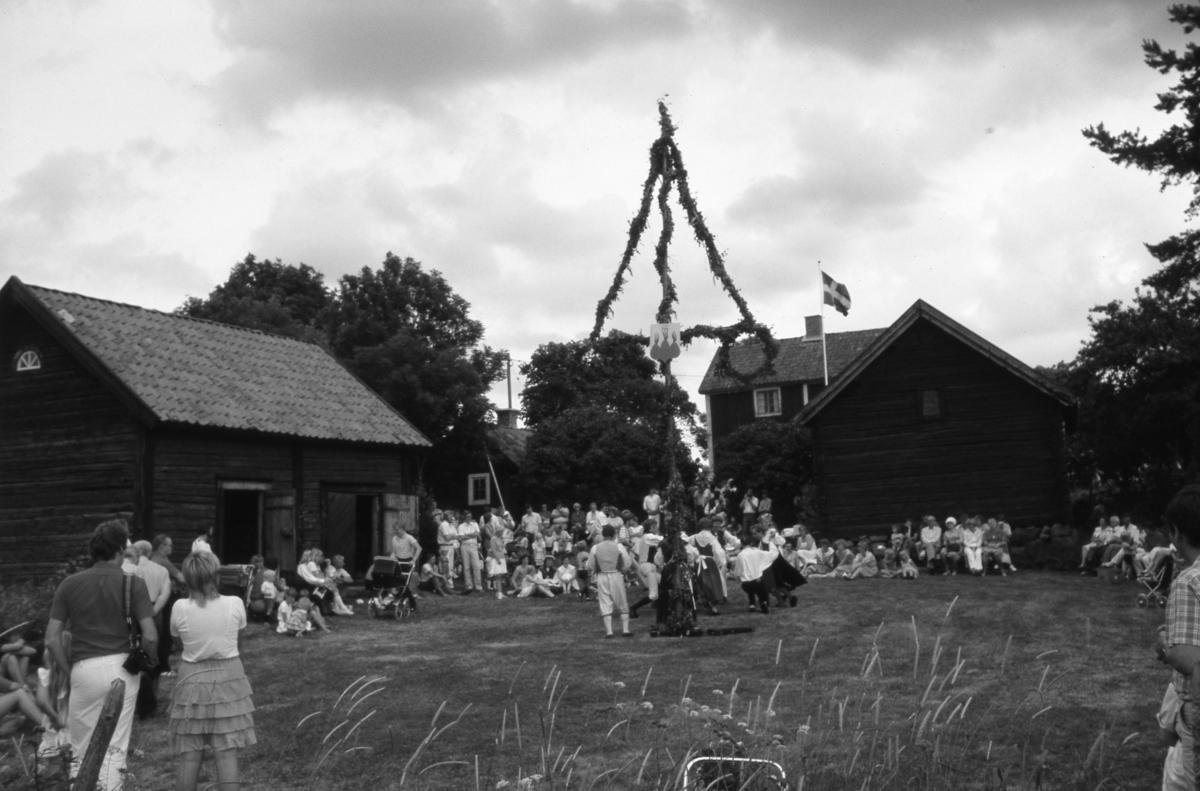 Midsommarfirande vid hembygdsgården Abramsgården i Medåker. Midsommarstången är rest och flaggan hissad. Publiken är utspridd. En barnvagn skymtar.