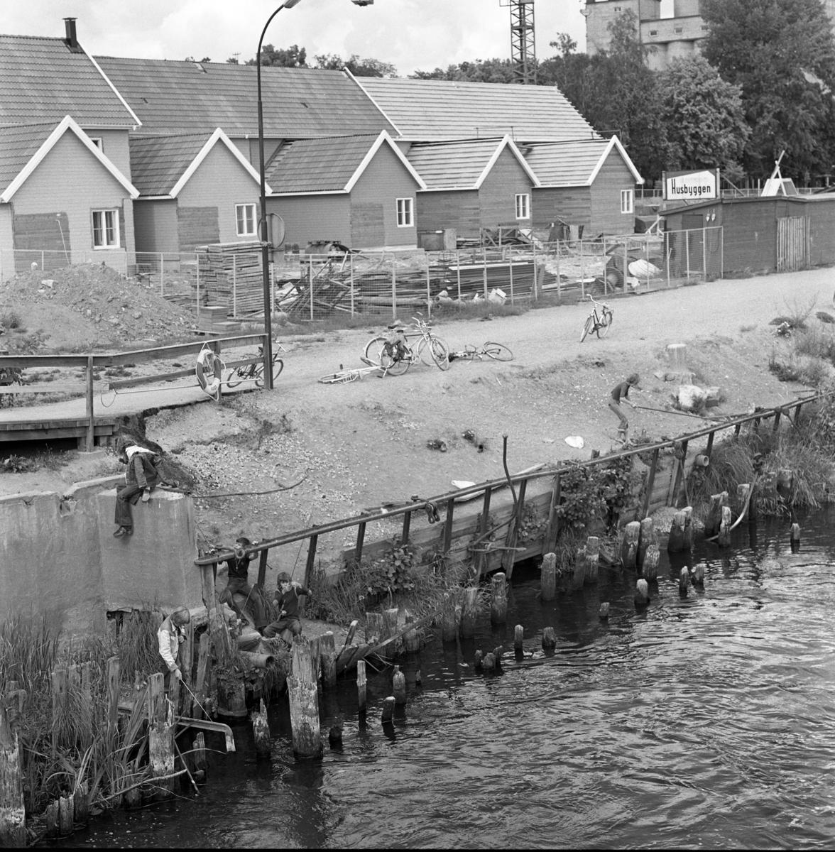 """Nybygge i kvarteret Herrgården, nordost om Herrgårdsbron. Adressen är Östra Hamngatan. Parhusen under byggnation. Det står """"Husbyggen"""" på en skylt. Några pojkar metar i Arbogaån. I bakgrunden, till höger, ses Lantmännens silo."""