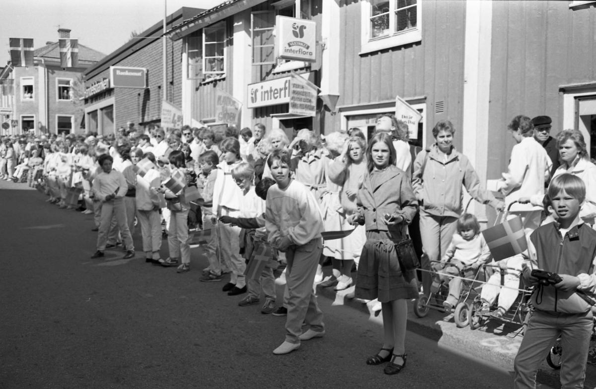 Människor kantar Nygatan, utanför Interflora och Handelsbanken och bankomaten. Skolungdomar med flaggor. I Arboga firas 550-årsminnet av Sveriges första riksdag. Kungaparet och höga politiker gästar staden. Riksdagsjubileet 1985.