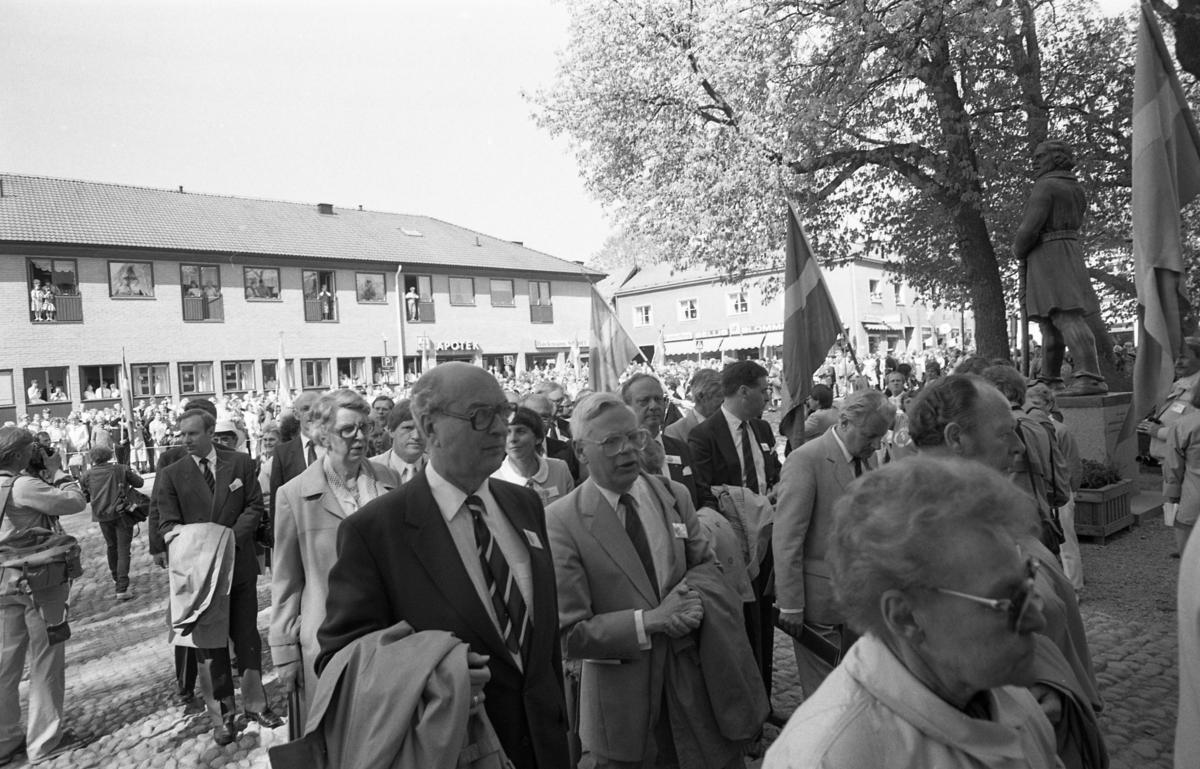 Riksdagsjubileet. I Arboga firas 550-årsminnet av Sveriges första riksdag. Politiker, så väl lokala som på riksplanet, är på väg in i Heliga Trefaldighetskyrkan. Pressen är på plats. Engelbrekt, firandets upphovsman, blickar ner från sin sockel. I bakgrunden ses Apoteket, Backmans Sport och Bellis Blommor. Allmänheten hålls på behörigt avstånd, på andra sidan Järntorget. Flaggorna vajar.