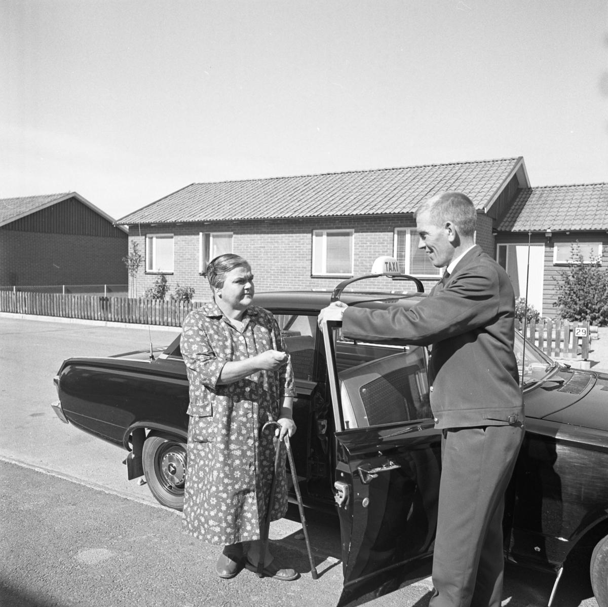 En kvinna ska åka taxi. Hon har en käpp i handen. Den uniformerade chauffören håller upp bildörren.