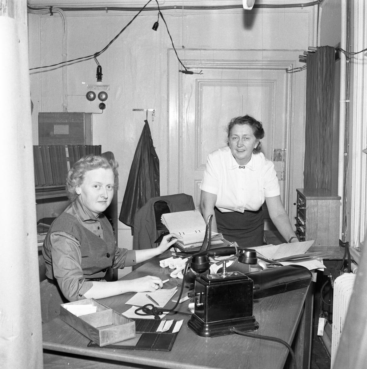 Televerket. Arbetet fortsätter trots skadorna efter branden i fastigheten på Nygatan. En kvinna sitter vid ett skrivbord. Hon har en pärm uppslagen. En telefon står på bordet. En annan kvinna står bredvid skrivbordet. En lampsladd hänger i taket. Läs om Telefonen i Arboga och branden på Televerket 1956 i Arboga Minnes årsbok 1993.