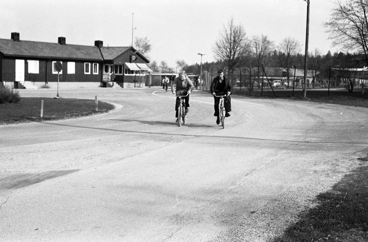 Två män cyklar hemåt efter en arbetsdag på CVA, Centrala Verkstaden Arboga. I bakgrunden ses byggnaden där vakten sitter och till höger om den, grinden, som alla måste passera.