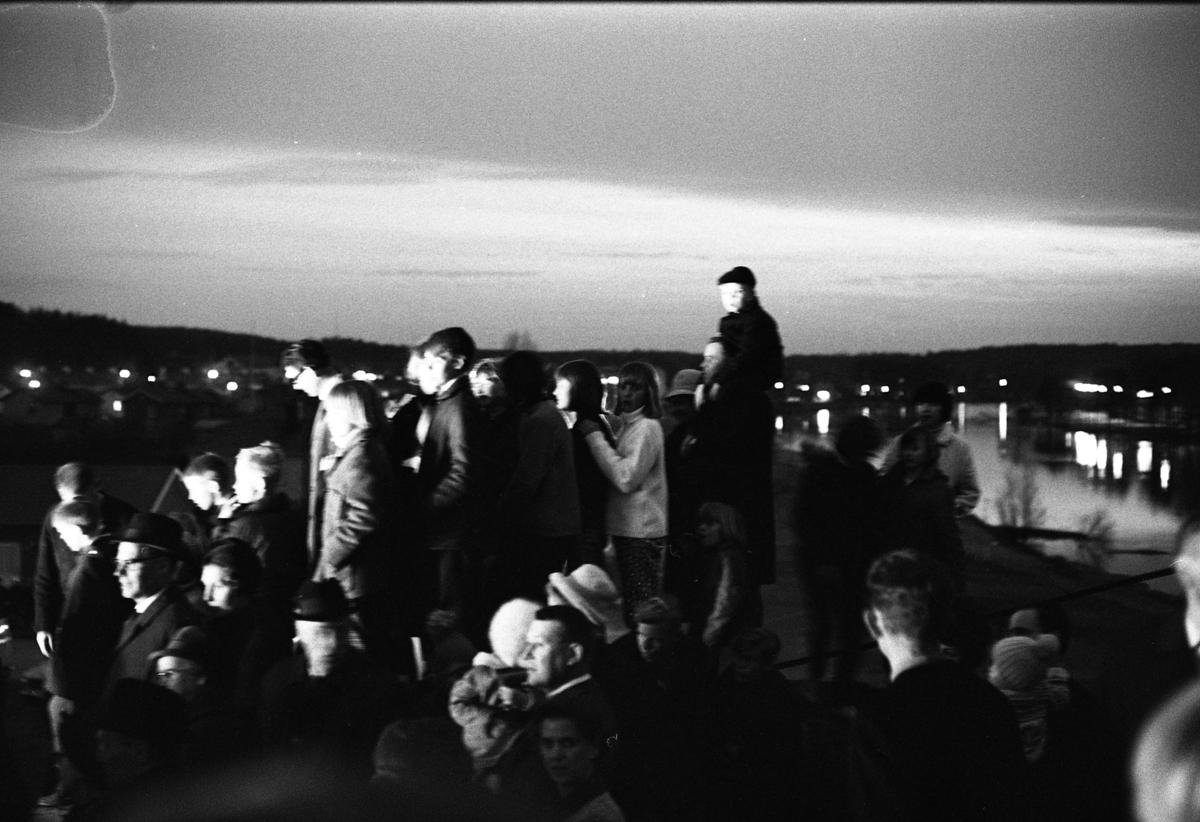 Valborgsmässoafton. Sista april. Vårens ankomst firas med brasa på Stenlöpet.  Publiken värmer sig vid elden. I bakgrunden ses Arbogaån.