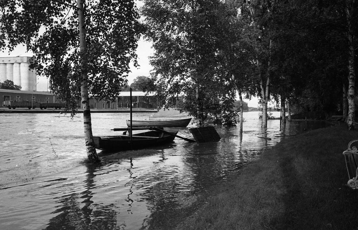 Vårfloden. Arbogaån har svämmat över på den södra sidan. Vattnet når upp över björkstammarna, en brygga är delvis under vatten. Två roddbåtar flyter. Mitt emot ses järnvägsvagnar vid hamnen och Lantmännens silo.