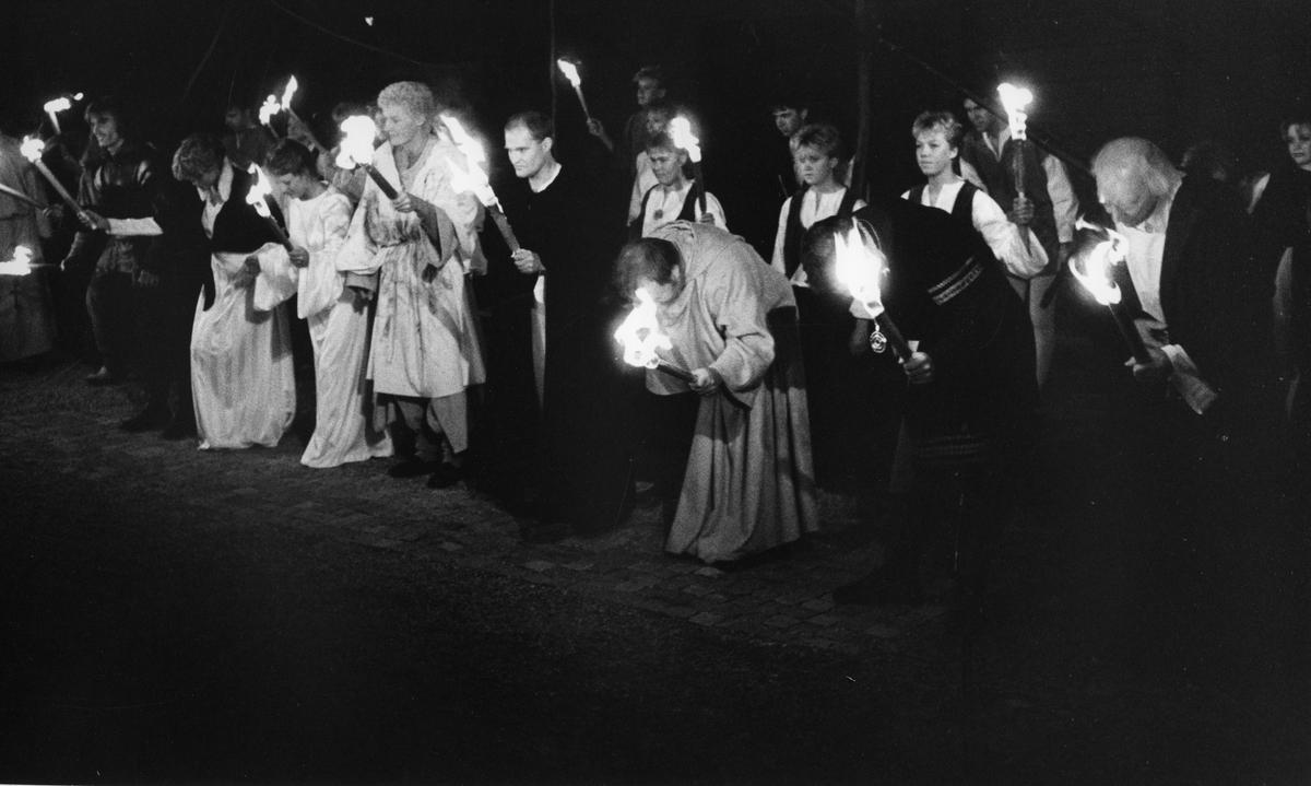 """Bygdespelets Vänner tackar för applåderna. De har just framfört skådespelet """"Giv oss fred"""" på museets innegård. De två bröderna; Lasse Sommar (längst till vänster) och Florentin (blond, med ljus särk och fackla i handen) har ledande roller. Florentin spelas av Matts Deubler/Mats Deubler. """"Giv oss fred"""", även kallat """"Arbogaspelet"""", är ett teaterstycke skrivet av Rune Lindström 1961. Handlingen, som är inspirerad av Arbogas klosterhistoria, är förlagt till början av 1500-talet. Uruppförandet skedde den 11 augusti 1962 och Rune Lindström spelade Engelbrekt Gertsson. Lions Club i Arboga stod för arrangemanget. Föreställningarna regnade bort och det blev ett stort ekonomiskt bakslag för föreningen. Spelet har framförts igen; 1987, 1988, 2012 och 2015 av medlemmar i """"Bygdespelets Vänner""""."""