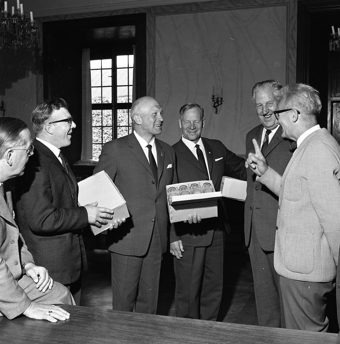 """Vänortsbesök från Hollola. Gästerna har fått, eller överlämnar, en gåva. Den leende mannen, till höger, är Folke Pettersson (Folkpartist i stadsfullmäktige) och mannen som """"läxar upp"""" de andra är Jonas Carlsson. De befinner sig i Rådhuset."""