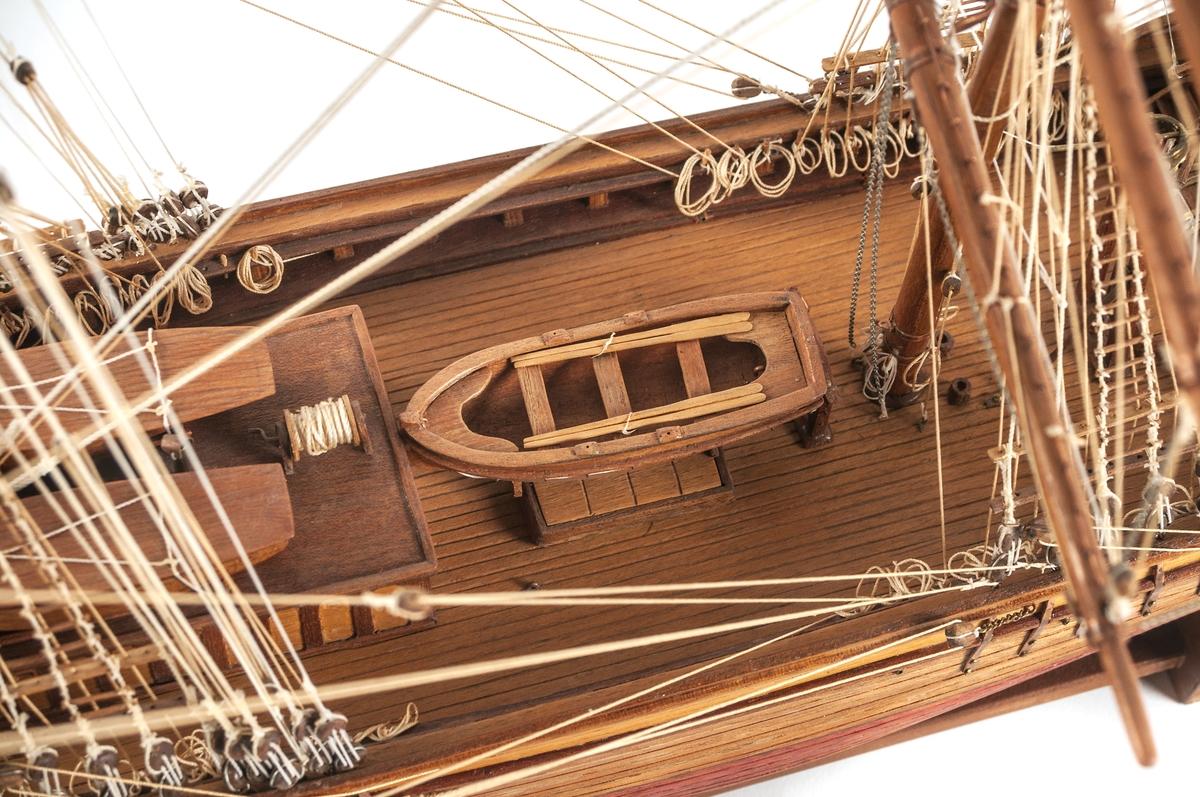 """Fartygsmodell, bark, i trä. Omålad. Tremastad. Förgyllda ornamnet på akterpartiets sidor samt överst på akterspegeln. Därunder en förgylld namnbräda med blå text och inramning """"GYDA GEFLE"""". Originalet byggt vid Parsgrund. Förlist 1918. Modell efter foto, mätbrev samt egna erfarenheter av segling med GYda. Skala 1:60."""