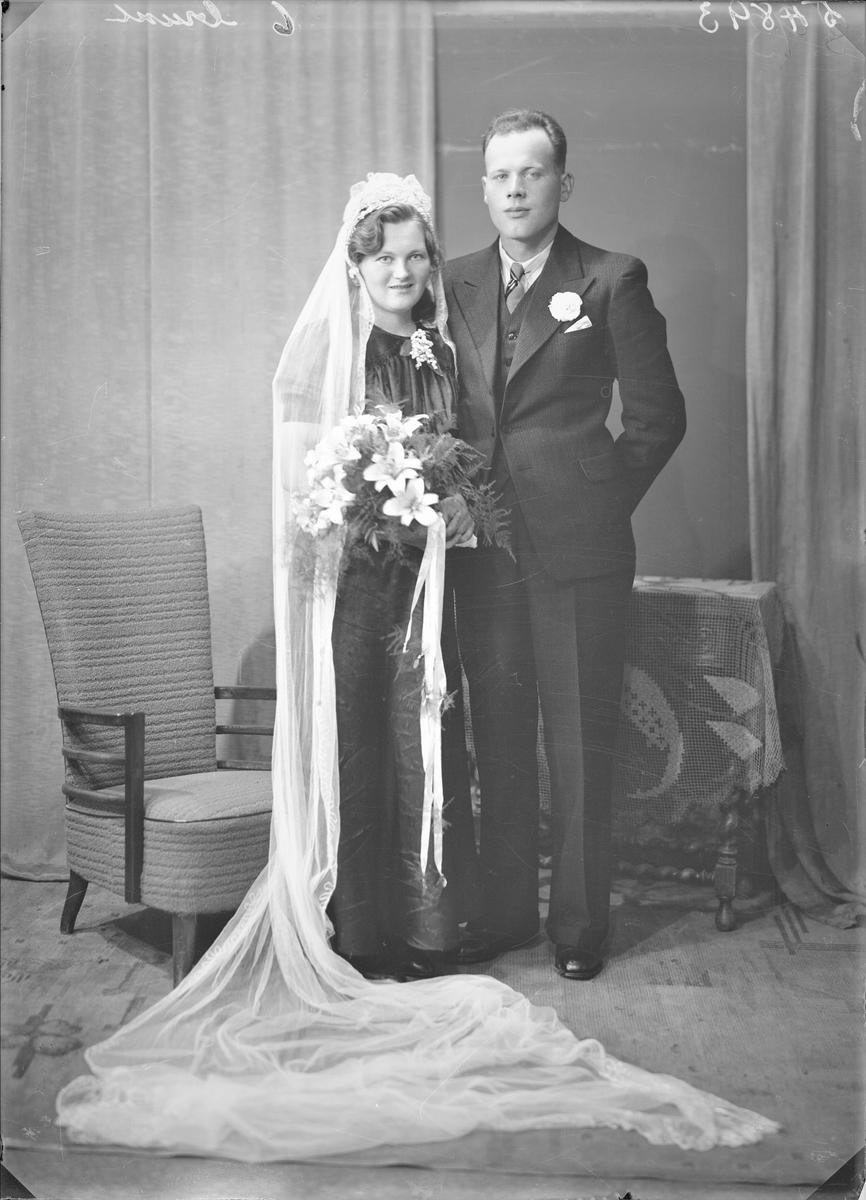 Portrett. Gruppe på to. Ung mann i mørk dress, mørk vest, hvit skjorte, mørk stripet slips og blomst i knappehullet. Ung kvinne i mørk kjole, langt lys slør, tiarra og blomsterpynt i front av kjolen. Blomsterbukett i hendene. Brudepar. Bestilt av Nils Næss. Stol. Karmøy
