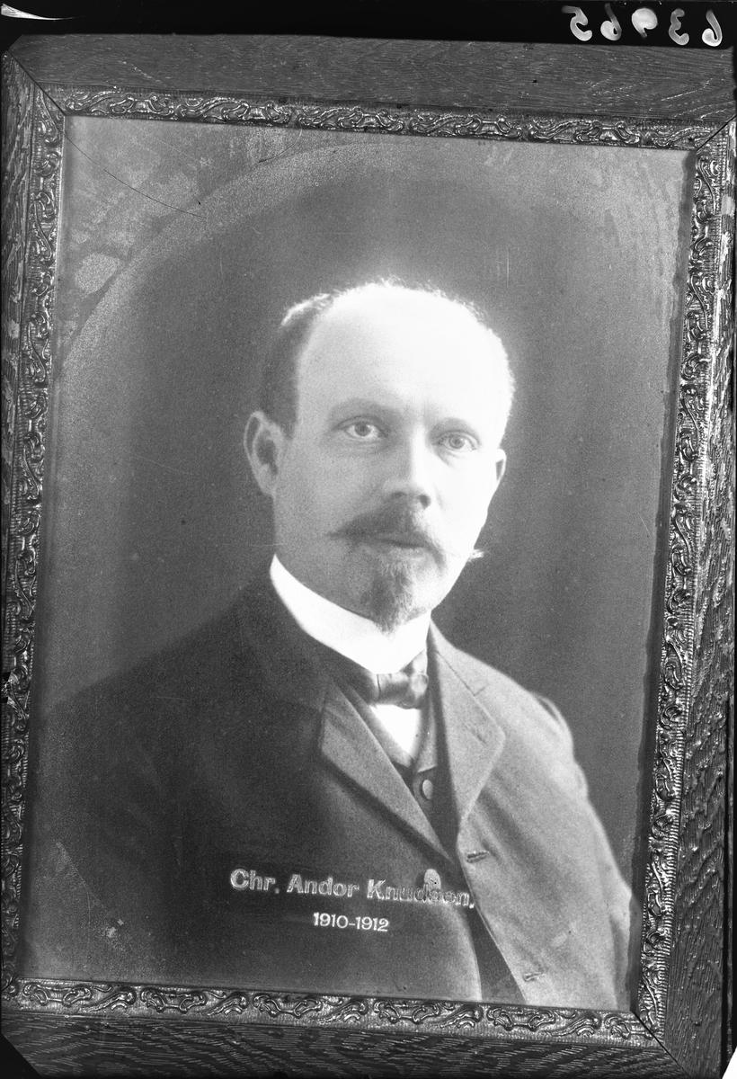 Portrett. Kopi av foto i ramme. Mann med lite hår, bart og flippskjegg i mørk stripet dress, hvit skjorte og mørkt sløyfe. Tekst på foto; Chr. Andor Knudsen 1910-1912. Bestilt av Haugesund Postkontor.